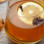 A glass of amber coloured drink with a lemon slice, start anise and a clove in it.