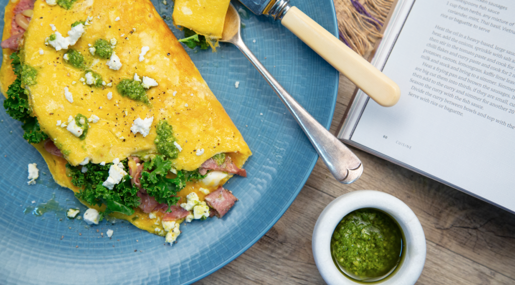 An omelette with pink meat , feta and green on blue plate and small pot of pesto.