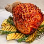 A whole baked ham and grilled pineapple pieces
