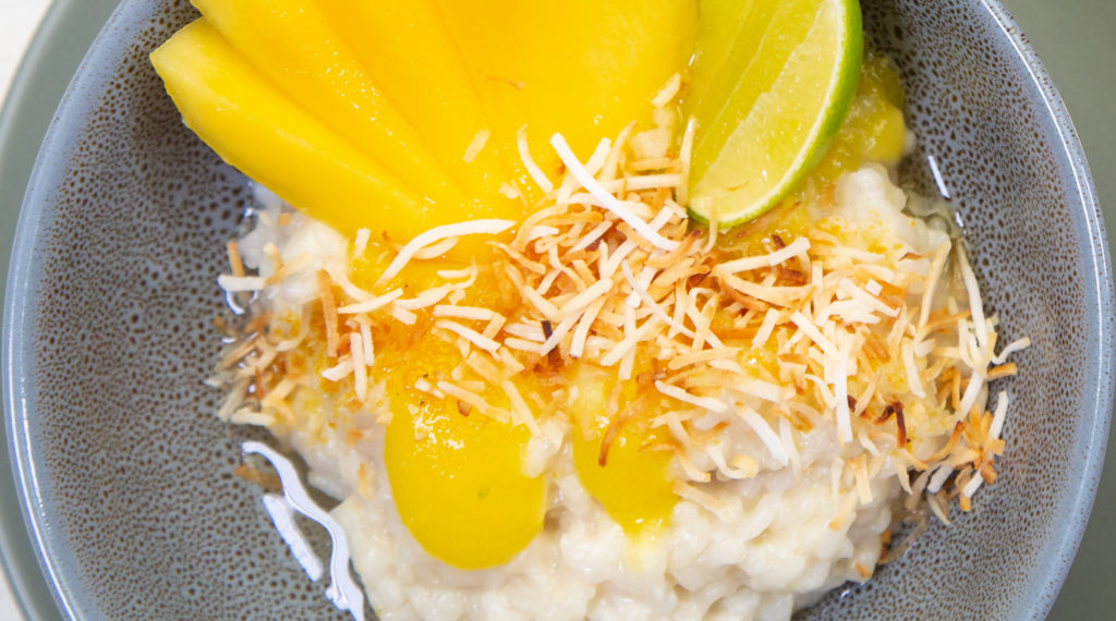 A bowl of white rice pudding topped with yellow fruit pieces and coconut.