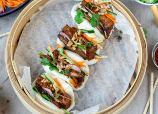 Top view of a bamboo steamer lined white paper and 4 bao buns filled with brown filling on it. Surrounded by chopsticks and small bowls filled with food.