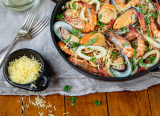 A frypan filled with cooked seafood on white cloth with small dish of grated cheese and forks