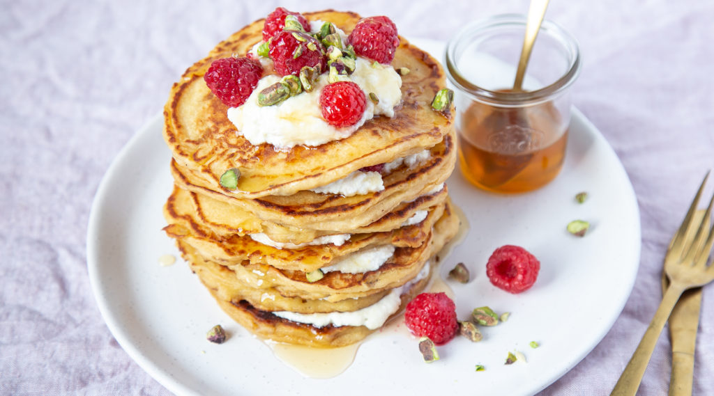 Pancakes stack with white cream and raspberries, and a jar of syrup.