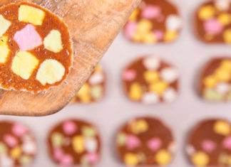 Slices of colourful lolly cakes in the background, one slice on a wooden spatula close up in front