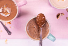 3 mugs of hot chocolate with spoons on pink background