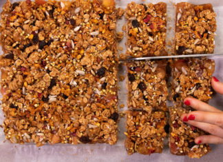 A top view of a large granola slice, a hand holding right bottom side and knife cutting into it just above.