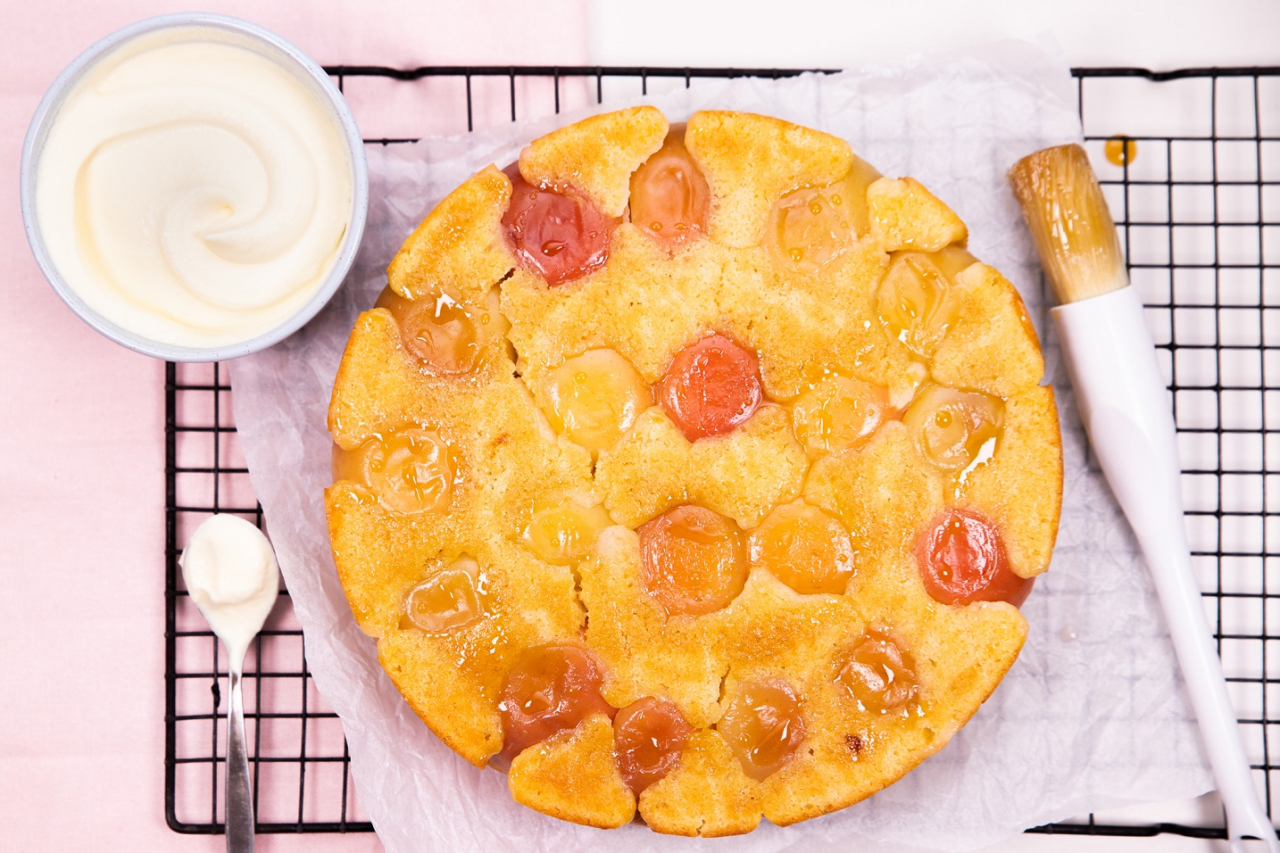 A round fruit embedded cake and a pastry brush, teaspoon,a small pot of cream on a wire rack.