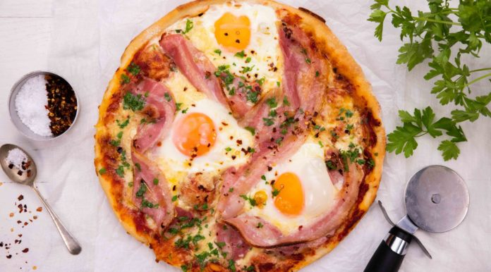 3 eggs and bacon strips on a pizza and a pizza cutter, spoon & green herb.