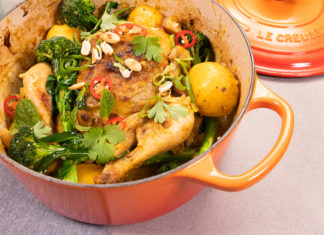 A orange casserole pan with a lid, filled with a whole cooked chicken topped with greens and chill