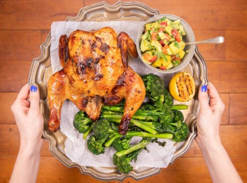 Hands holding a silver tray with whole roast chicken,broccoli, lemon half and a pot of salsa on it over wooden board