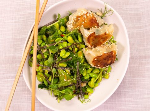 3 dumplings on bed of green bean salad in an oval white bowl with chopsticks on pale pink cloth.