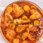 Chicken pieces and apricot halves in reddish brown sauce in a white casserole pan with handles on white board