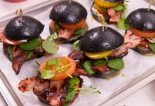 6 small black round bun sandwiches with skewers on a paper lined tray