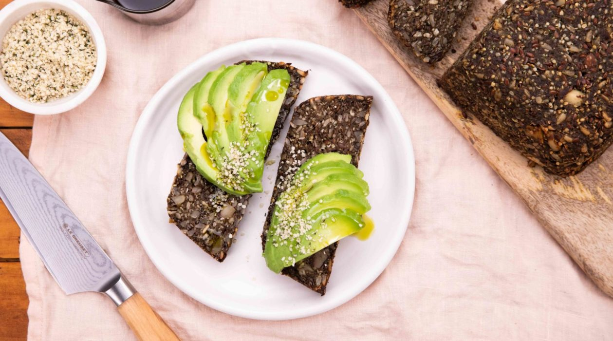 2 slices of dark brown bread with avocado slices on top on a white round plate next to the brown loaf on wooden board with a knife and a small pots of seeds