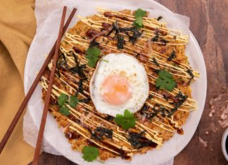 A brown pancake topped with a fried egg and pices of nori & herb and chopsticks on wooden board