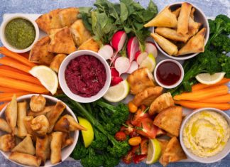 Small fried snacks, tomato sauce and hummus in small bowls on a rectangle tray among cut vegetables and lemon wedges.