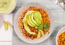 Two big bowls of brown chilli with avocado slices on top
