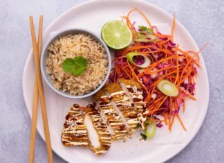 Chicken katsu served with brown rice and colourful salad on a plate