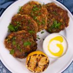 Four round fritters on a white plate with a pot of white sauce and charred lemon