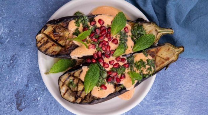 2 aubergine halves topped with pink sauce, herbs and red berries
