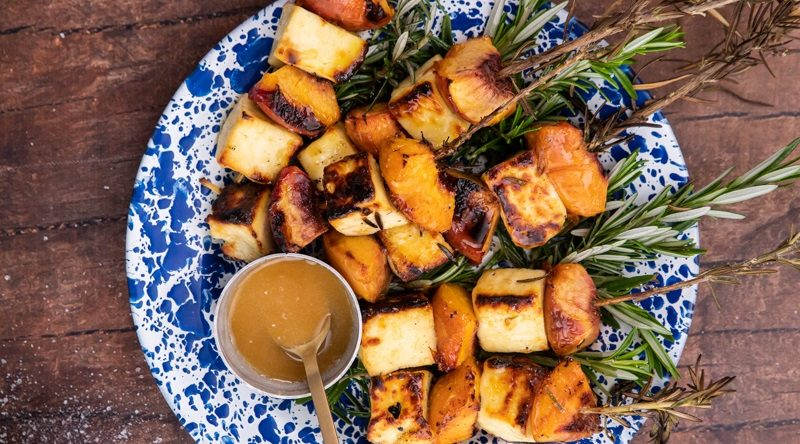 grilled cheese and peach skewers on blue plate and a pot of honey