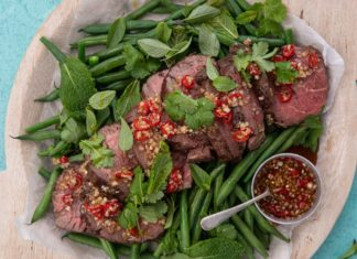 cooked beef slices on bed of green beans with a pot of red sauce