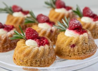 7 cakes with cream and red berries on a glass plate