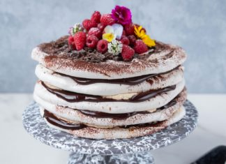 chocolate cream sandwiched layer cake with raspberries and flowers on top