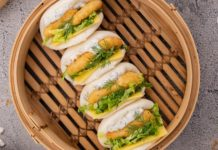 4 bao buns filled with fish nuggets on a bamboo steamer