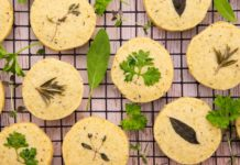 Round biscuits topped with herbs on wire rack