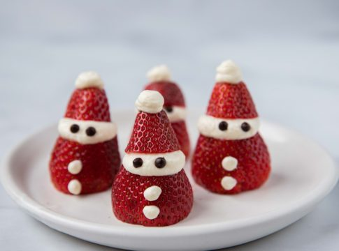4 Santa strawberries on a white plate