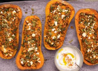 4 stuffed butternut squash halves on a baking tray with a pot of aioli