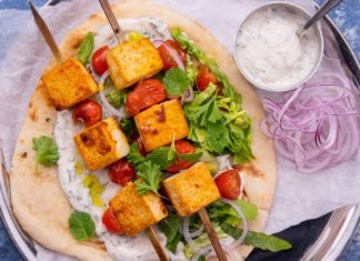 Two brown cube tofu and tomato skewers on bed of green salad on a flatbread with a small pot of white sauce