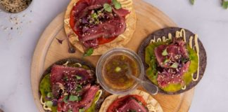 4 round tostada with beef on a round wooden board and a small grass pot and a spoon in middle