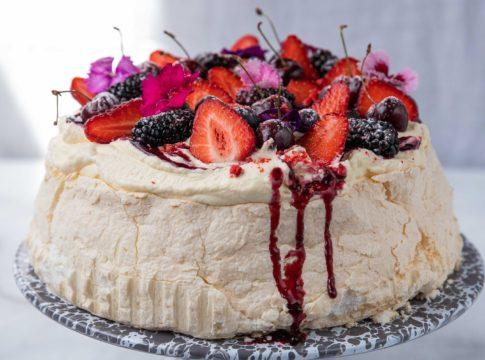 red fruit topped pavlova on a marble plate