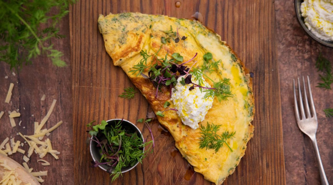 A half circle shaped yellow omelette topped with herbs and a blob of white cheese on a wood board and a small pot of greens and a fork