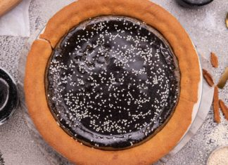 black round pie and small pot, spoons on bench top