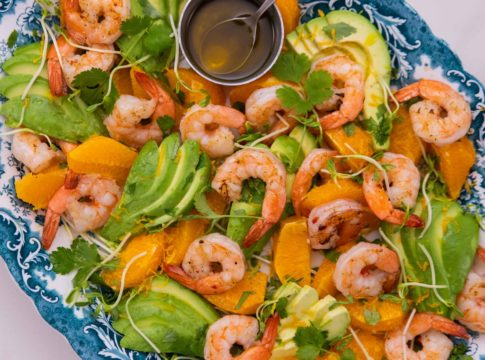 Prawns , Avocado slices, orange segments mixed on a blue oval plate on marble top.