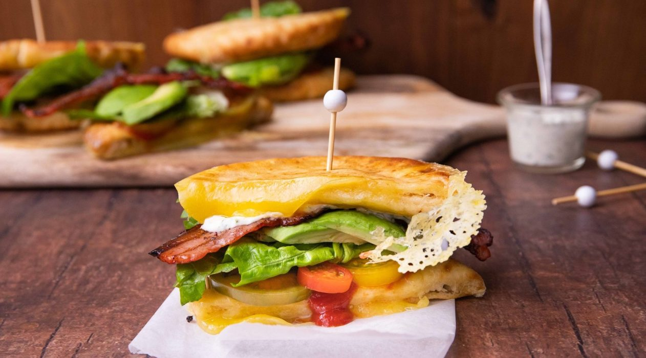 A side shot of toasted sandwich with avocado, bacon and tomato filling on a white board with some more in back ground.