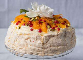 orange and red fruit pavlova with a white rose on top on a glass cake stand