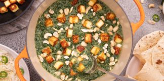 A orange casserole dish with green curry with brown cubes surrounded by flat breads and pot of rice