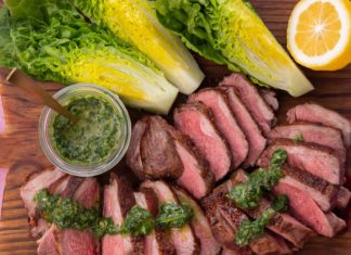 Meat slices and lettuce pieces on a wooden board with half lemon and a pot of green sauce