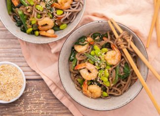 Two large bowls with noodles topped with prawns and greens with chopsticks and two small bowls on pink fabric.
