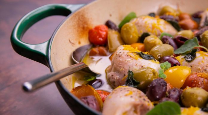 Chicken pieces, tomatoes and olives in a green pan with a handle on wooden board