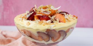 A glass bowl full of yellow cream and red and orange coloured fruit on pink & white background