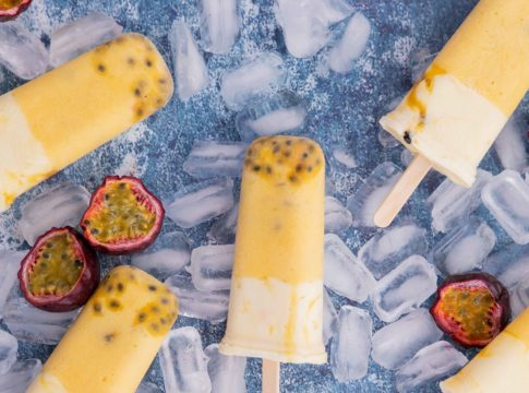 5 yellow and white ice blocks and passionfruit halves on ice cubes