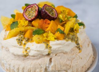 Orange and yellow coloured fruit topped pavlova on white marble table