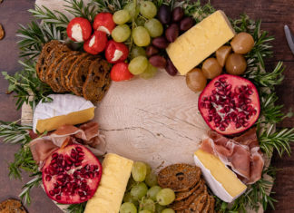 cheese, crackers and fruits placed in a ring on a wooden board