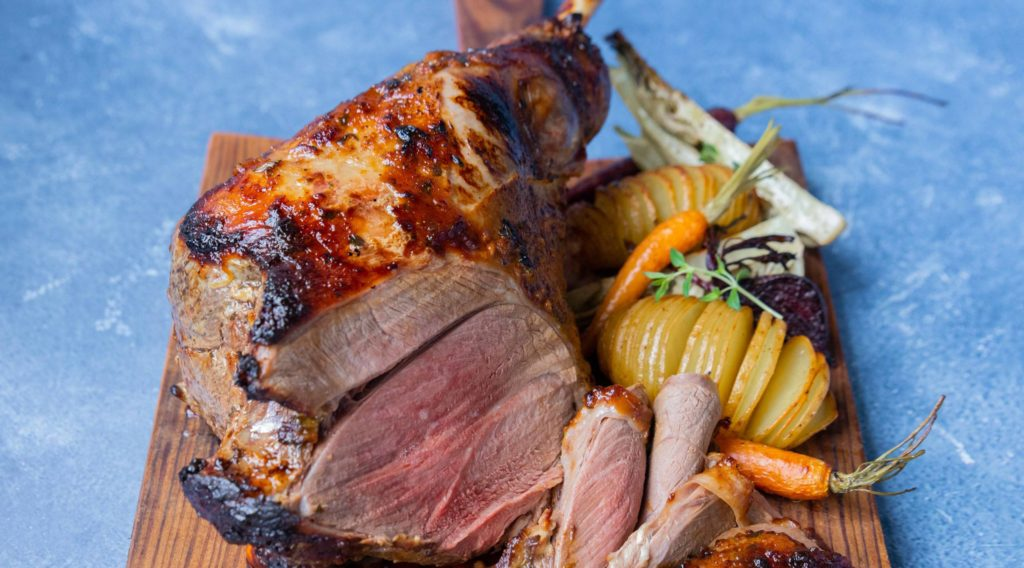 Lamb roast on bone with roasted potato and vegetables on a wooden board on blue background
