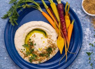 Hummus paste and carrots on a blue round plate on blue surface with a pot of brown dukka.